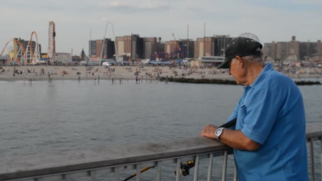medium shot of an old white male finishing off of a pier in coney island, new york with the beaches, amusement parks, and housing projects in the... - pier stock videos & royalty-free footage
