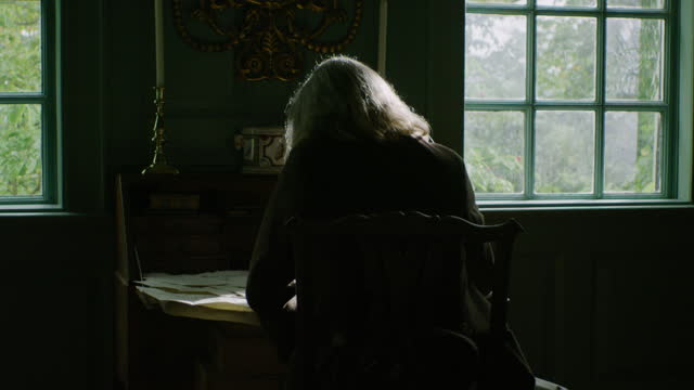vidéos et rushes de medium shot of an older man sitting in front of his desk and looking out the window - image du xviiième siècle