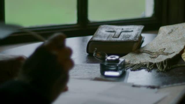 vídeos de stock e filmes b-roll de medium shot of an older man writing a letter with a quill - século xviii
