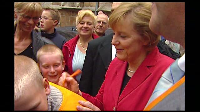 medium shot of angela merkel signing the t-shirts of two young boys at an election rally in germany; 2005. - 2005 stock-videos und b-roll-filmmaterial