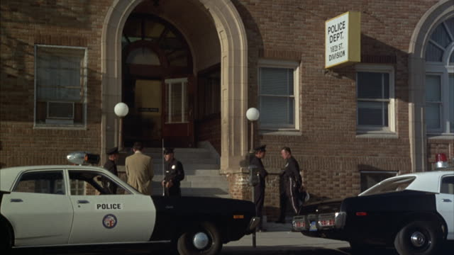 medium shot of arched entrance of division police station in san francisco with parked police cars and several policemen talking. - rettungsdienst mitarbeiter stock-videos und b-roll-filmmaterial