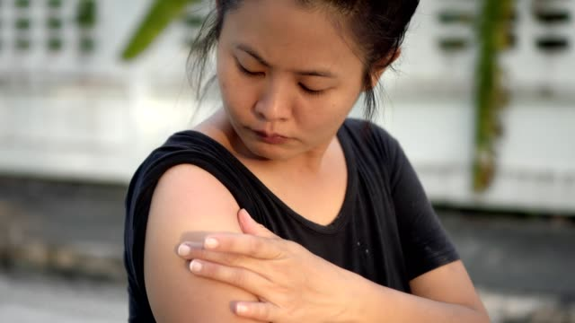 medium shot of asian women/young adult scratching arm - arm stock videos & royalty-free footage