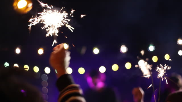 medium shot of audience hands holding sparklers at concert - concert stock videos & royalty-free footage