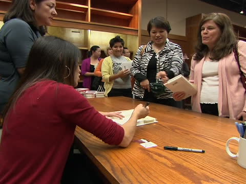 """medium shot of author amy chua signing her book """"battle hymn of the tiger mother"""" and talking with guests. chua set off quite a bit of controversy... - signierstunde stock-videos und b-roll-filmmaterial"""