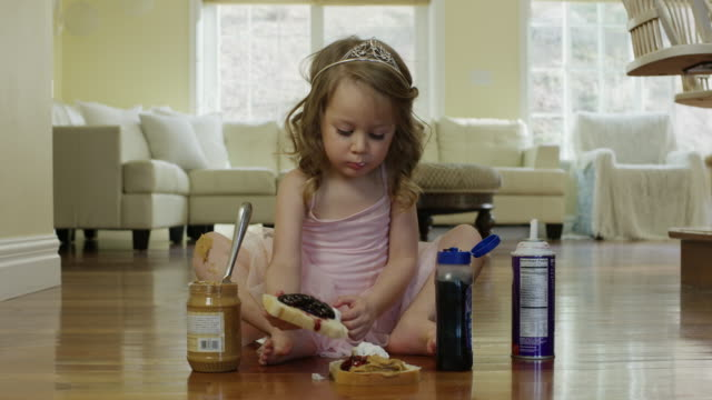 """medium shot of ballerina girl assembling sandwich on floor / cedar hills, utah, united states"" - preserve stock videos and b-roll footage"
