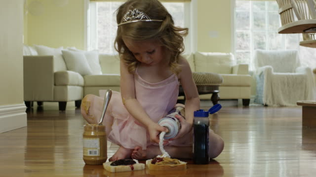 'Medium shot of ballerina girl spraying whipped cream on bread / Cedar Hills, Utah, United States'