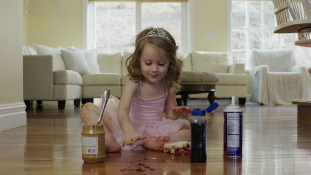 """Medium shot of ballerina girl spreading food on knee and floor / Cedar Hills, Utah, United States"""