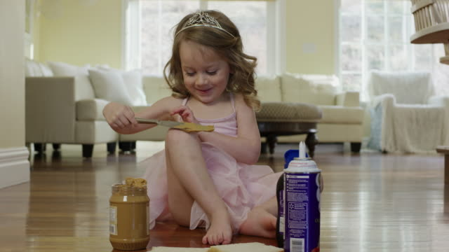 """Medium shot of ballerina girl spreading peanut butter on knee / Cedar Hills, Utah, United States"""