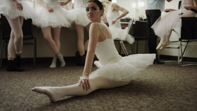Medium shot of ballerina stretching on floor / Salt Lake City, Utah, United States