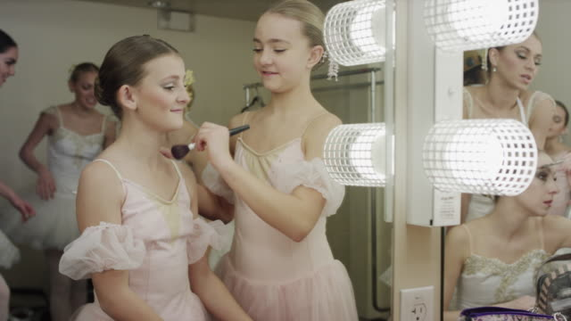 Medium shot of ballerinas applying makeup in dressing room mirror / Salt Lake City, Utah, United States