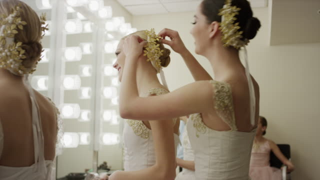 vídeos de stock, filmes e b-roll de medium shot of ballerinas preparing in busy dressing room / salt lake city, utah, united states - feminidade