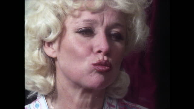 medium shot of barbara windsor applying red lipstick to her lips, pressing them together and blowing herself a kiss in the mirror; 1981. - headshot stock videos & royalty-free footage