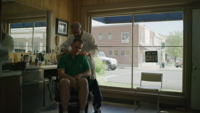 medium shot of barber brushing hair from shoulders of customer / pleasant grove, utah, united states - barber chair stock videos & royalty-free footage