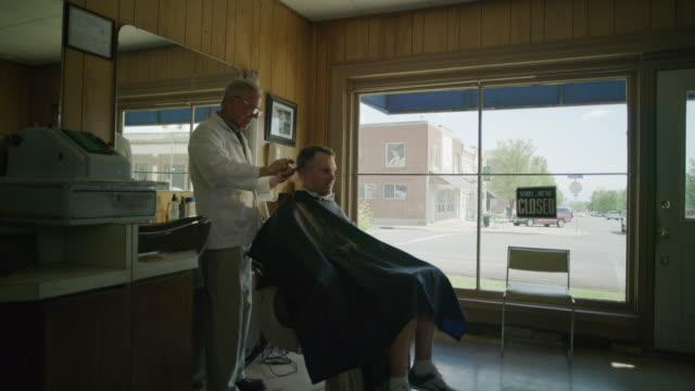 medium shot of barber cutting hair of customer / pleasant grove, utah, united states - haare schneiden stock-videos und b-roll-filmmaterial
