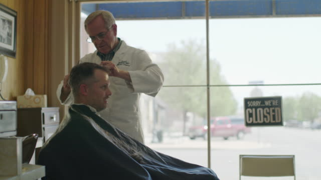 medium shot of barber cutting hair of customer / pleasant grove, utah, united states - barber chair stock videos & royalty-free footage