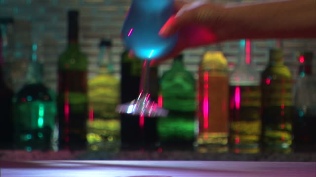 medium shot of bartender placing tropical cocktail on bar. - tropical cocktail stock videos & royalty-free footage