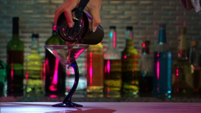 medium shot of bartender pouring a martini and adding garnish at bar. - garnish stock videos & royalty-free footage