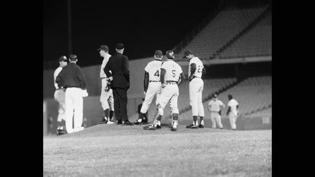 medium shot of baseball players, coach and umpire meeting at mound of pitcher on baseball diamond, dodger stadium, los angeles, california, usa - medium group of people stock videos & royalty-free footage