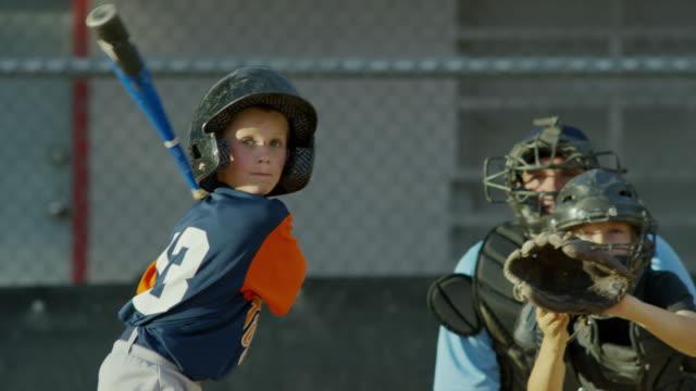 Medium shot of batter hitting baseball / American Fork, Utah, United States