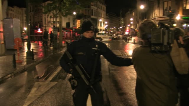 stockvideo's en b-roll-footage met medium shot of belgium policeman in uniform that reads politie police zoom out to officers blocking off street at night and setting up a barricade... - (war or terrorism or election or government or illness or news event or speech or politics or politician or conflict or military or extreme weather or business or economy) and not usa