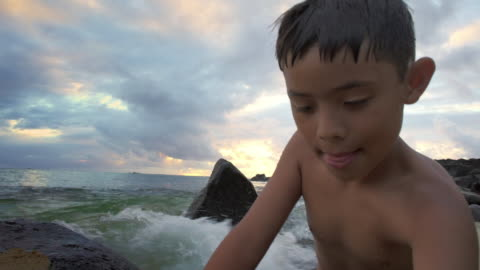 stockvideo's en b-roll-footage met medium shot of boy playing in a rising tide - alleen jongens