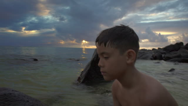 medium shot of boy playing in a shallow tide - nackter oberkörper stock-videos und b-roll-filmmaterial
