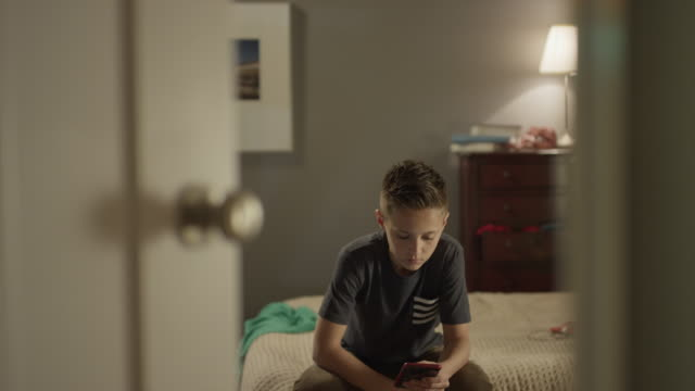 Medium shot of boy using cell phone closing bedroom door for privacy / Cedar Hills, Utah, United States