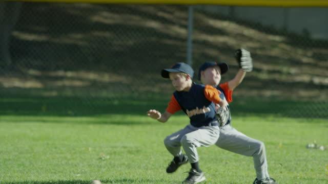 vídeos y material grabado en eventos de stock de medium shot of boys colliding in baseball game / american fork, utah, united states - caer
