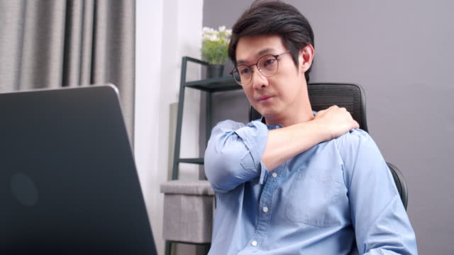 medium shot of business asian man working on laptop and feel pain on his shoulder while sitting and doing business at home all day. muscle pain, health care concept. - cramp stock videos & royalty-free footage