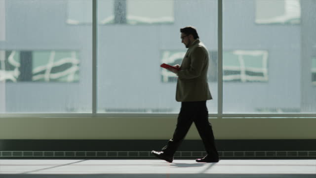 medium shot of businessman walking and using digital tablet / provo, utah, united states,  - provo stock videos & royalty-free footage