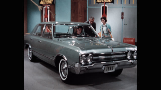 medium shot of car salesperson showing car to customer in showroom - car showroom stock videos & royalty-free footage