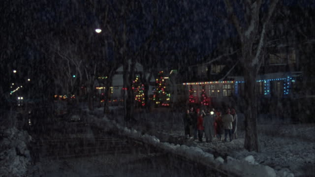Medium shot of carolers in a snowy residential area decorated for the holiday season.