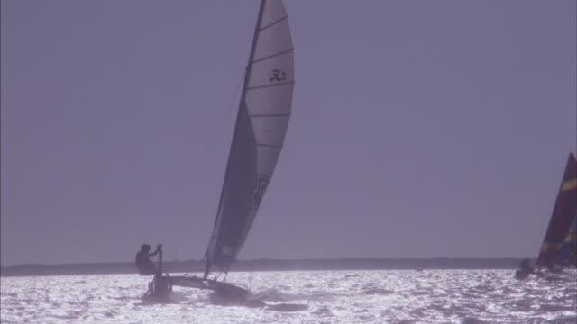 Medium shot of catamarans racing on open water.