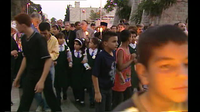 medium shot of children in gaza lead a candlelit march to remember the victims of the 9/11 attacks; 14th september, 2001. - waist up stock videos & royalty-free footage