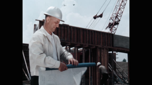 medium shot of civil engineer reading blueprint while standing at construction site with workers working in background - construction worker stock videos & royalty-free footage
