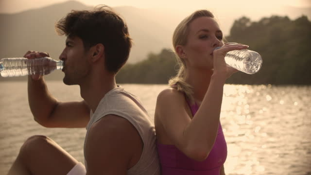 Medium shot of couple drinking water/Marbella region, Spain