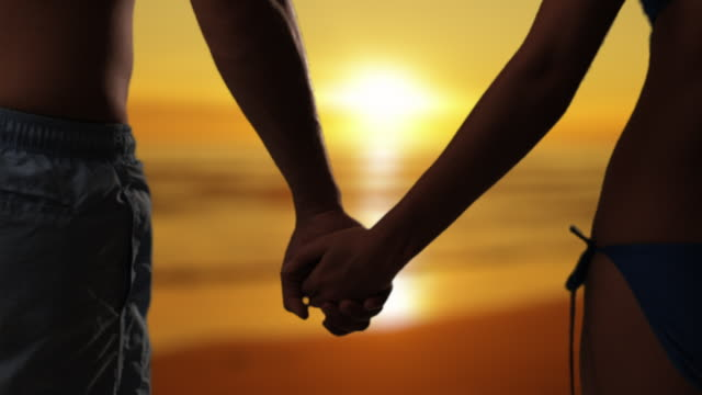 Medium shot of couple embracing on the beach at sunset/Marbella region, Spain