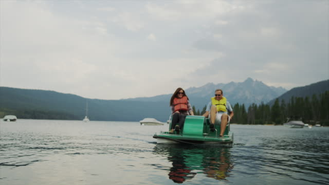 Medium shot of couple in pedal boat on lake / Redfish Lake, Idaho, United States