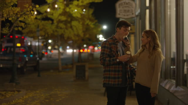 stockvideo's en b-roll-footage met medium shot of couple on sidewalk eating ice cream cones / provo, utah, united states - provo