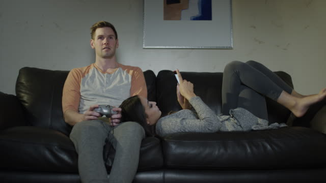 Medium shot of couple on sofa playing video game and texting / Cedar Hills, Utah, United States