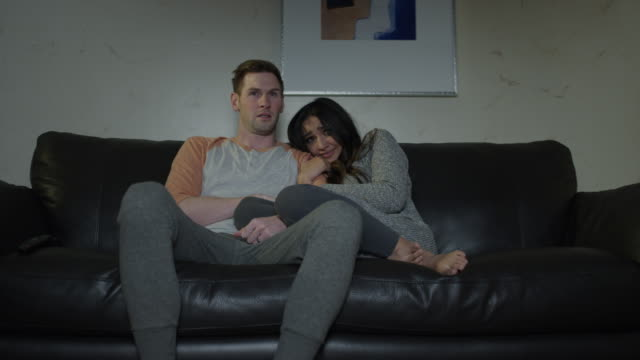 Medium shot of couple on sofa watching scary movie on television / Cedar Hills, Utah, United States