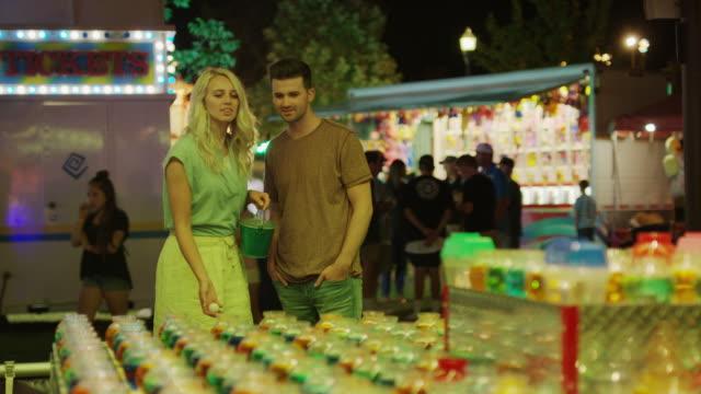 vidéos et rushes de medium shot of couple playing game at amusement park / pleasant grove, utah, united states - embrasser sur la bouche