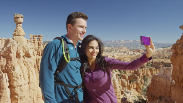 Medium shot of couple posing for cell phone selfie in canyon / Bryce Canyon National Park, Utah, United States