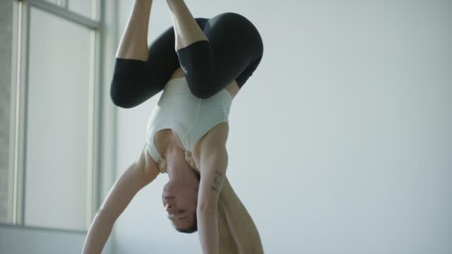 stockvideo's en b-roll-footage met medium shot of couple practicing acro yoga in studio / orem, utah, united states - benen gespreid