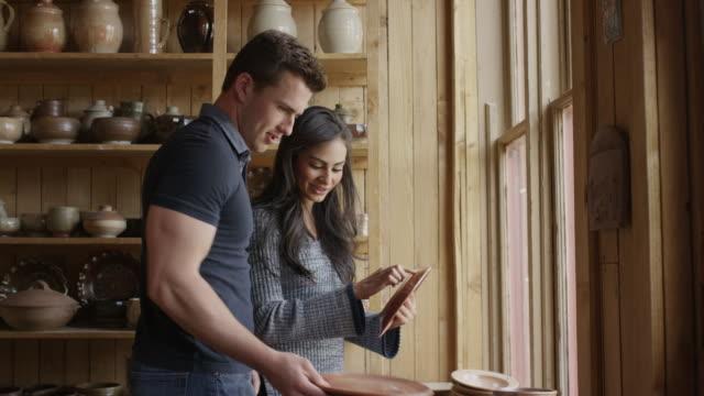 vídeos de stock, filmes e b-roll de medium shot of couple shopping in pottery store / spring city, utah, united states - camisa pólo