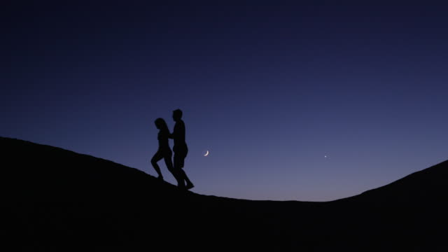 medium shot of couple silhouetted on hill against night sky / lake powell, utah, united states - lake powell stock-videos und b-roll-filmmaterial