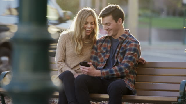 stockvideo's en b-roll-footage met medium shot of couple sitting on urban bench texting on cell phone / provo, utah, united states - provo