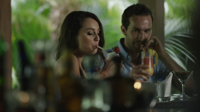 medium shot of couple toasting with tropical drinks in bar / arenal, la fortuna, costa rica - costa rica video stock e b–roll