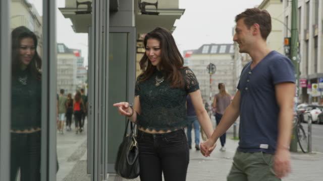 medium shot of couple window shopping in city / berlin, germany - schaufenster stock-videos und b-roll-filmmaterial