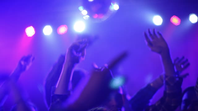Medium shot of crowd's hands up in air at concert